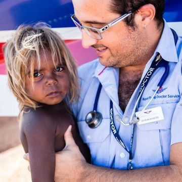 Image of doctor from Royal Flying Doctor Service holding Indigenous child