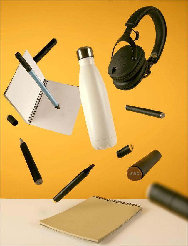 Penner, flasker og headset flyr i lufa –med en sterk gul bakgrunn.