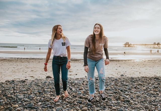 To unge jenter smilende på en strand. Foto