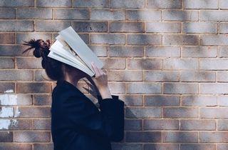 Person har gjemt seg bak en bok, kanskje i frustrasjon