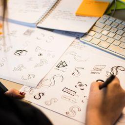Caroline lager grove skisser ulike versjoner av logoer for Sakte film på papir.