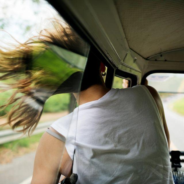Dame har hodet ut av bilvinduet i fart, håret blåser i vinden. Foto
