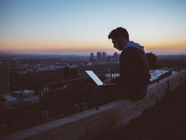 Person sitter på kanten av en bygning og bruker pcen i solnedgang