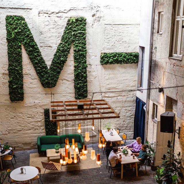 De ansatte i Kult Byrå sitter på et bord, drikker kaffe og prater i bakgården til Mesh.
