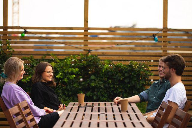 Kult gjengen sitter på et bord, drikker kaffe og smielr