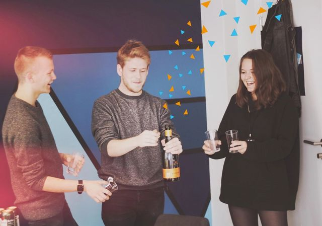 Kult-gjengen som spretter en champagne for å feire. Det er lagt til konfetti på bildet.