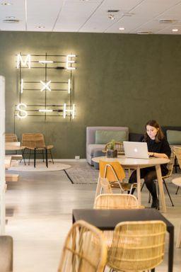 Vilde i Kult Byrå sitter på et bord, kosentrert og jobber på en macbook