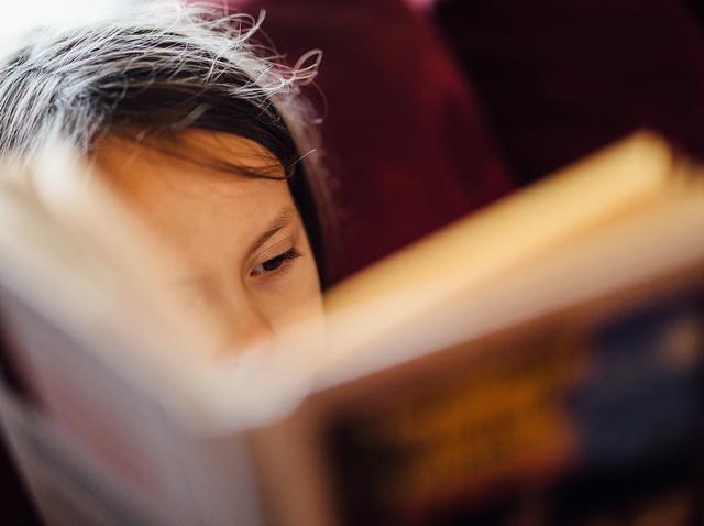 Lite barn som leser bok. Foto