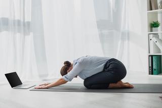 Dame gjør yoga på gulvet på kontoret, med laptop foran seg. Foto