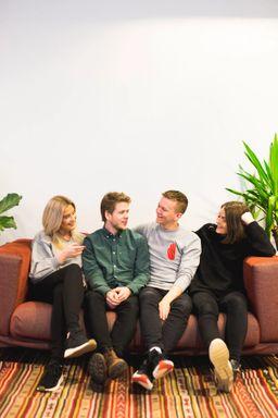 Kult gjengen sitter i en sofa og ler