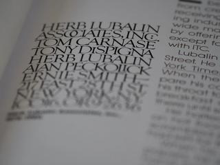 Side fra bok med to ulike fonter. Teksten i fokus er skrevet med kun store bokstaver. Foto.