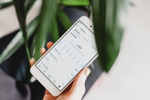 Person holder mobil som viser et utdrag av Google Analytics og webstatistikk