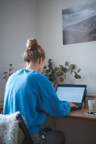 Jente sitter på hjemmekontor iført collegegenser og jobber på en laptop. Foto