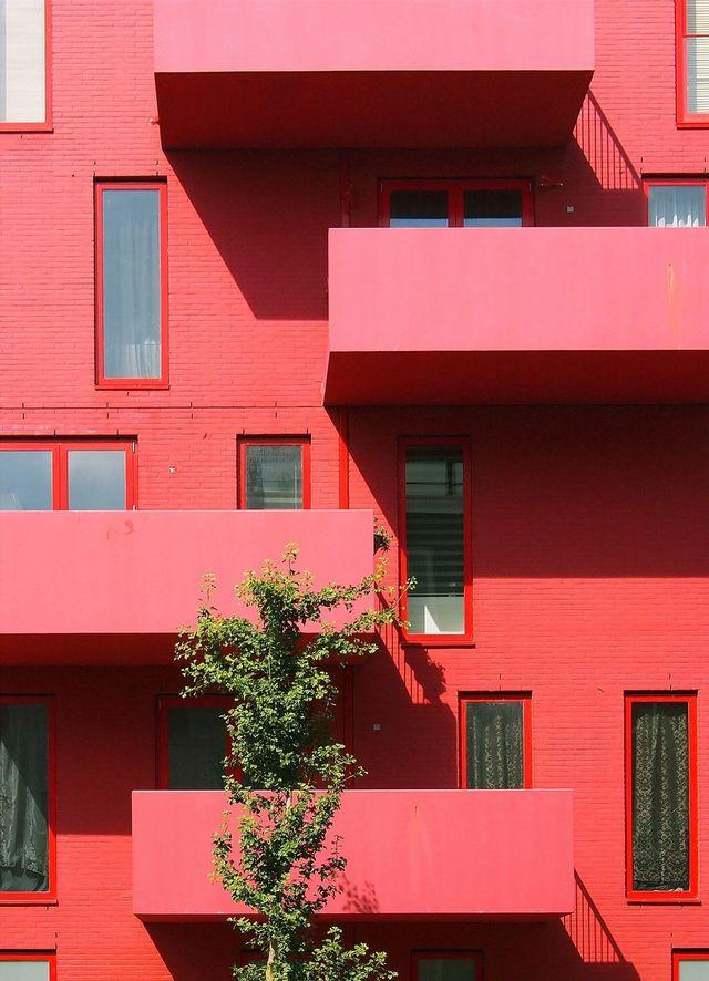 Rød bygning med fire balkonger. Kreativ arkitektur. Foto