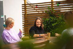 Caroline og Vilde i Kult Byrå sitter på et bord, drikker kaffe og prater