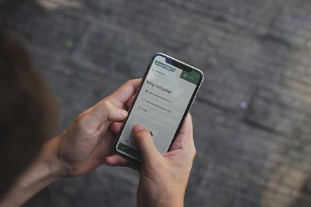 Bilde av person som holder mobil med nettside til Franzefoss. Velger container. Foto
