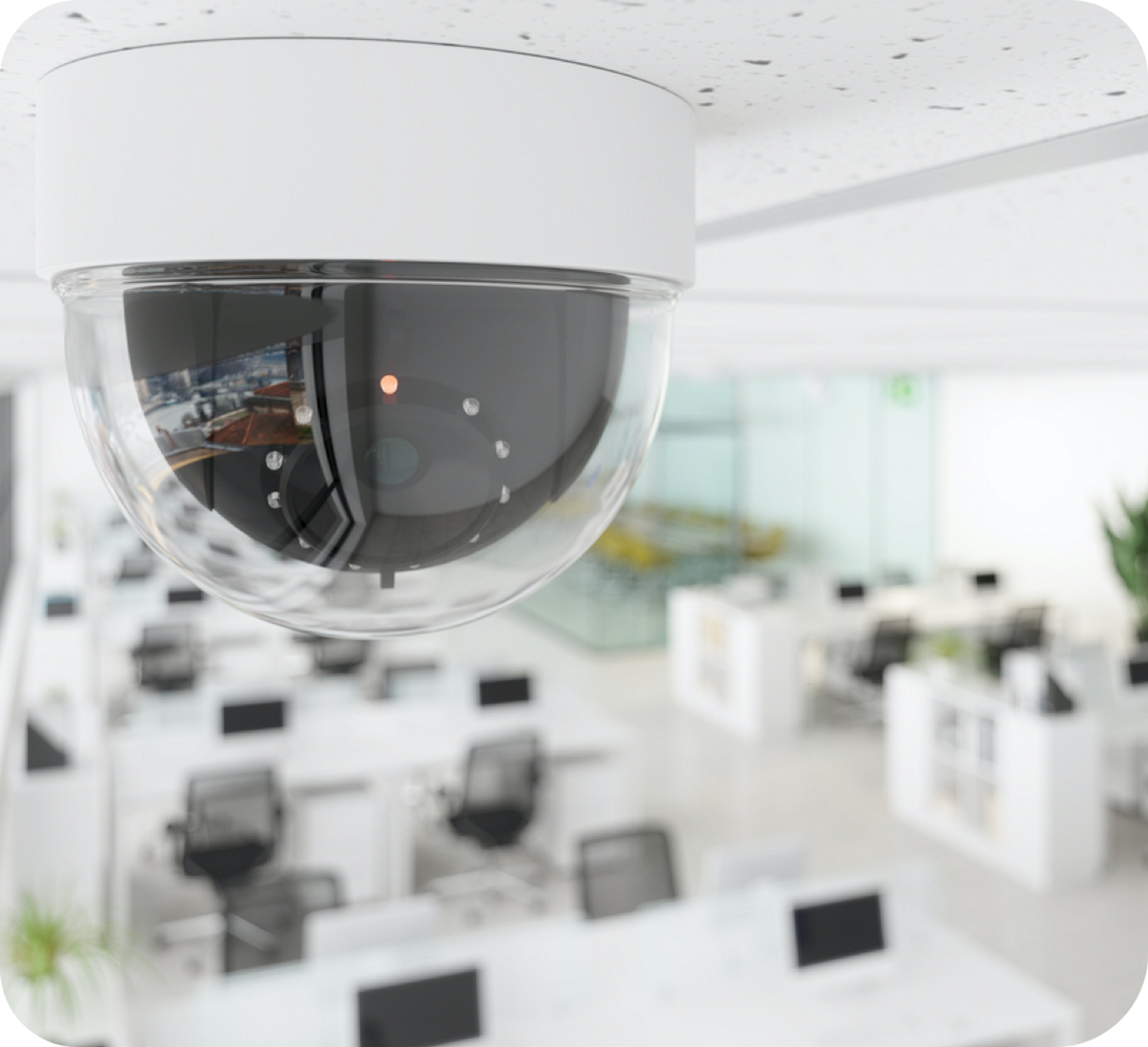 Picture of a security camera on the roof above office desks