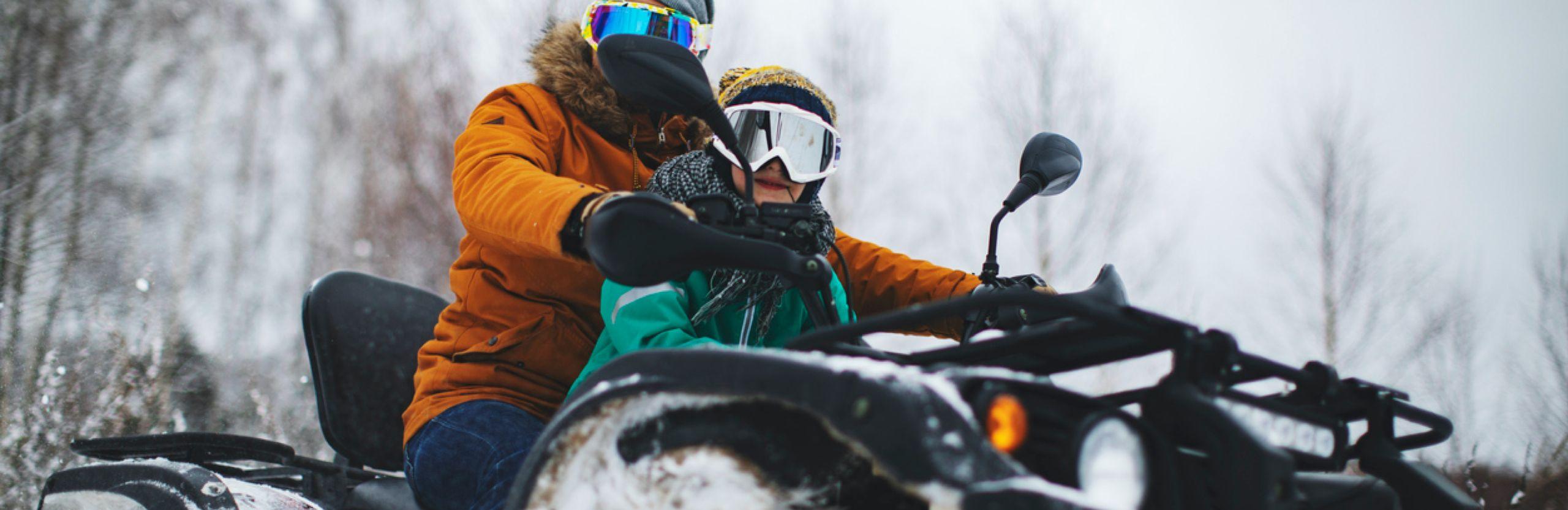 Photo d'un homme et d'un garçon sur un VTT dans la neige