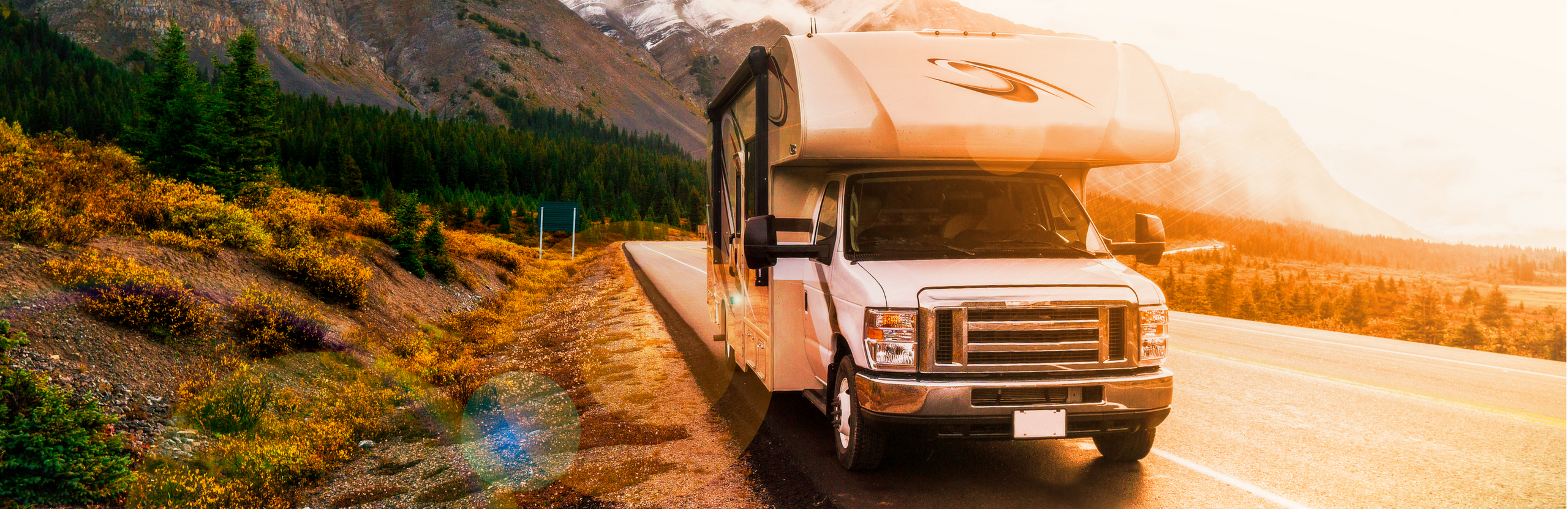 Picture of RV on a sunset road and boreal forest landscape