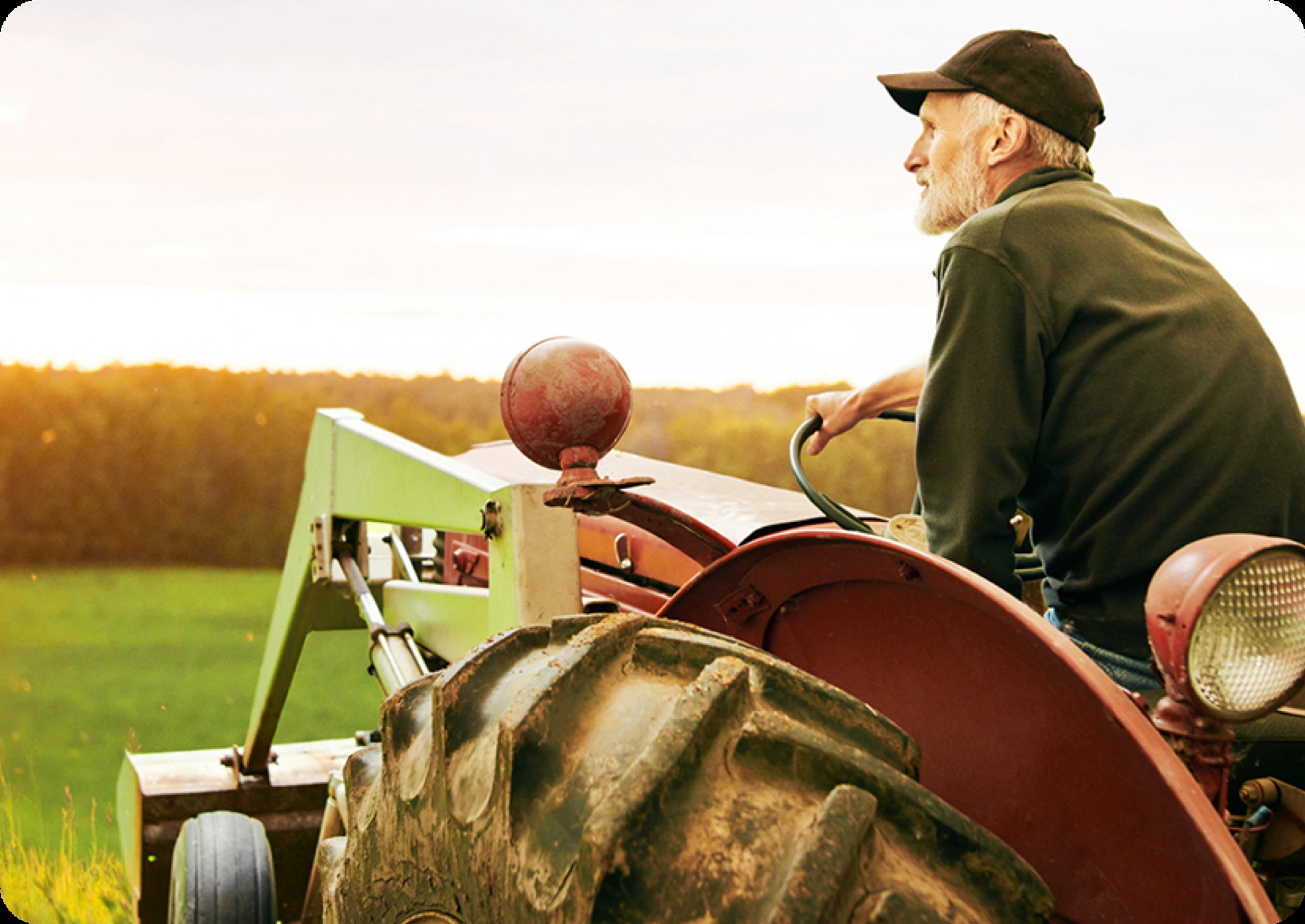 Photo d'un homme âgé conduisant un tracteur agricole