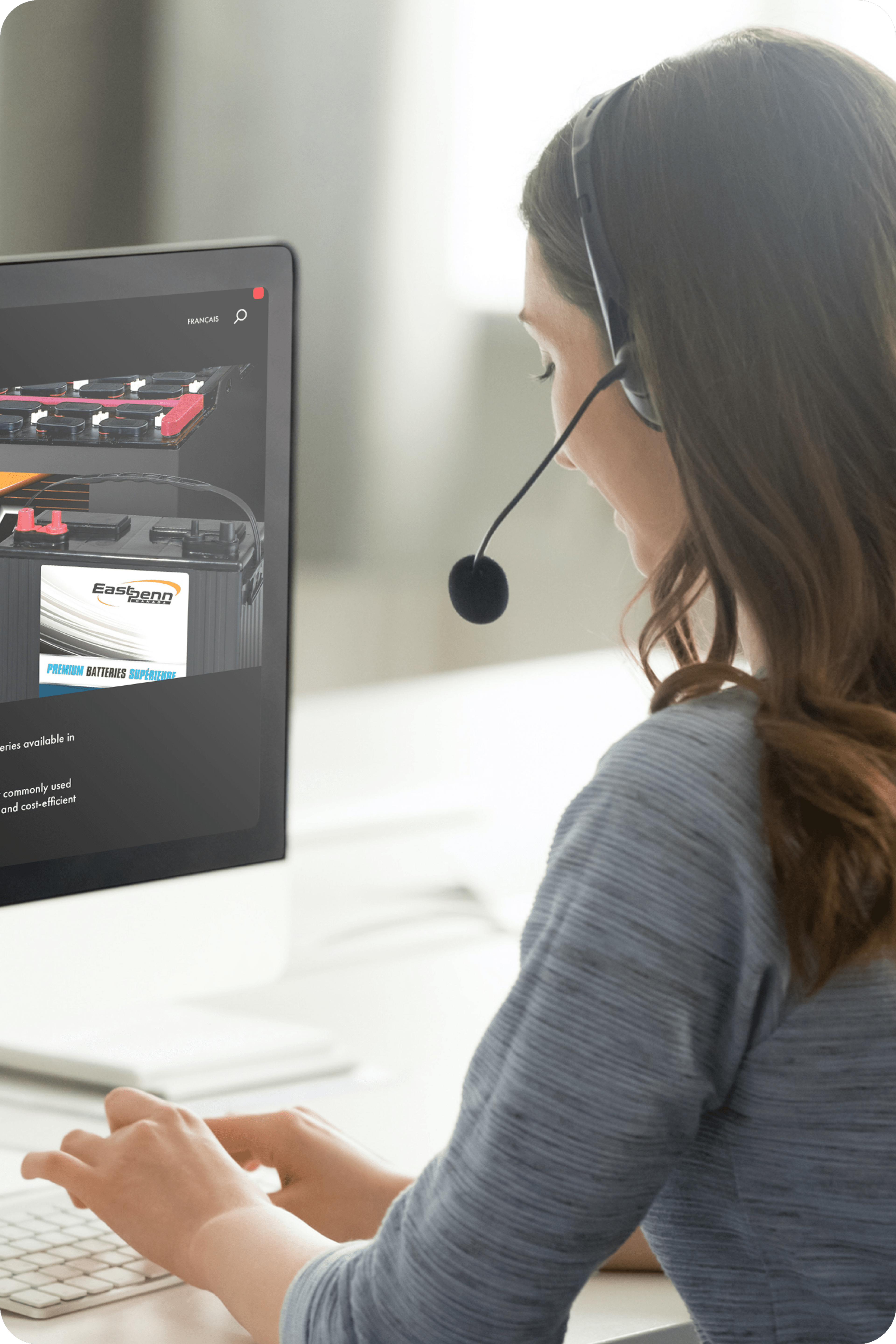 Picture of woman offering customer care via her headset while using a computer with two monitors showing images of East Penn car battery and East Penn website