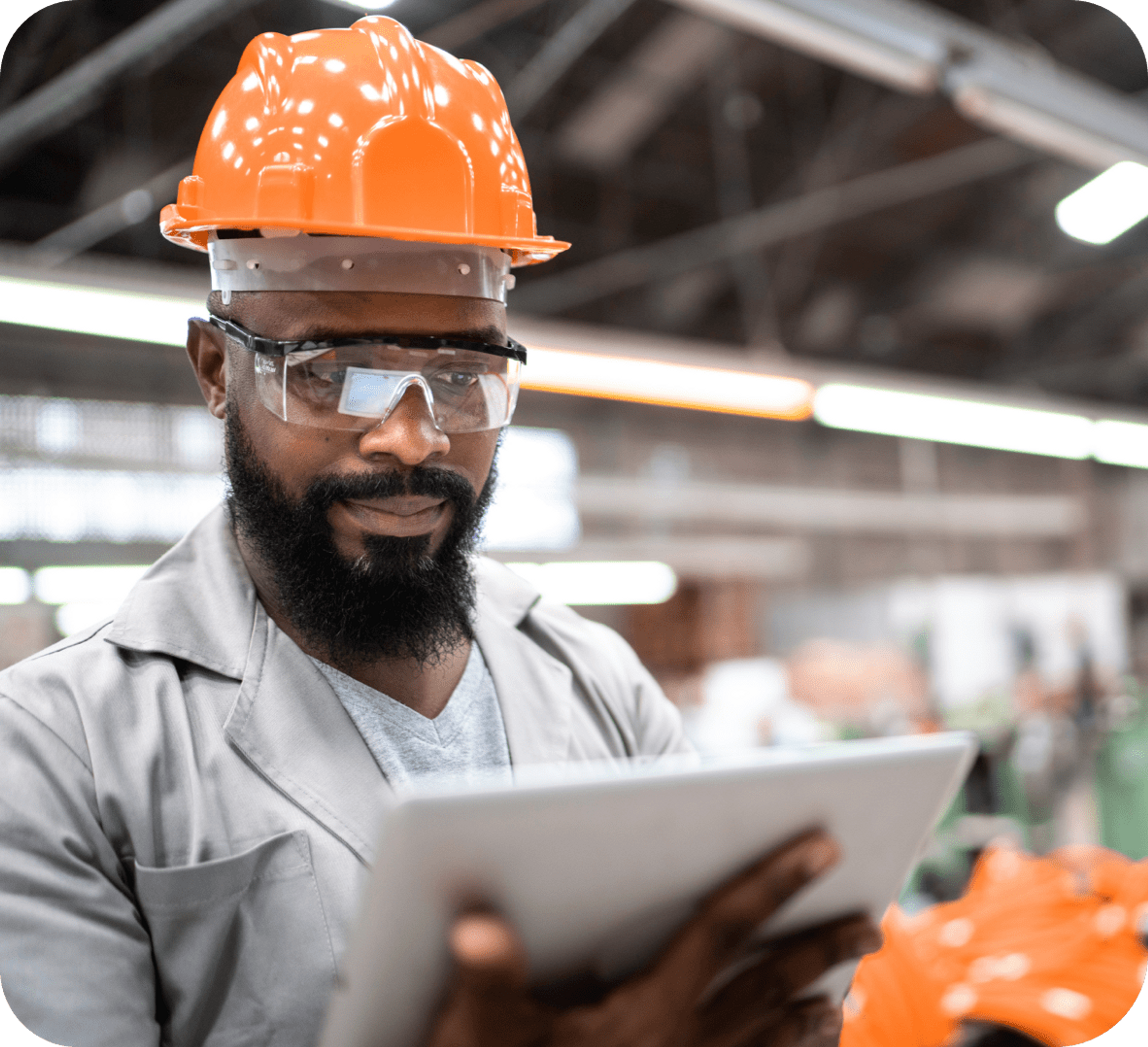 Picture of African man wearing safety glasses, orange hard hat, gray coat and gray t-shirt while holding a white clipboard and seems to be reflecting about the data he is reading on that clipboard