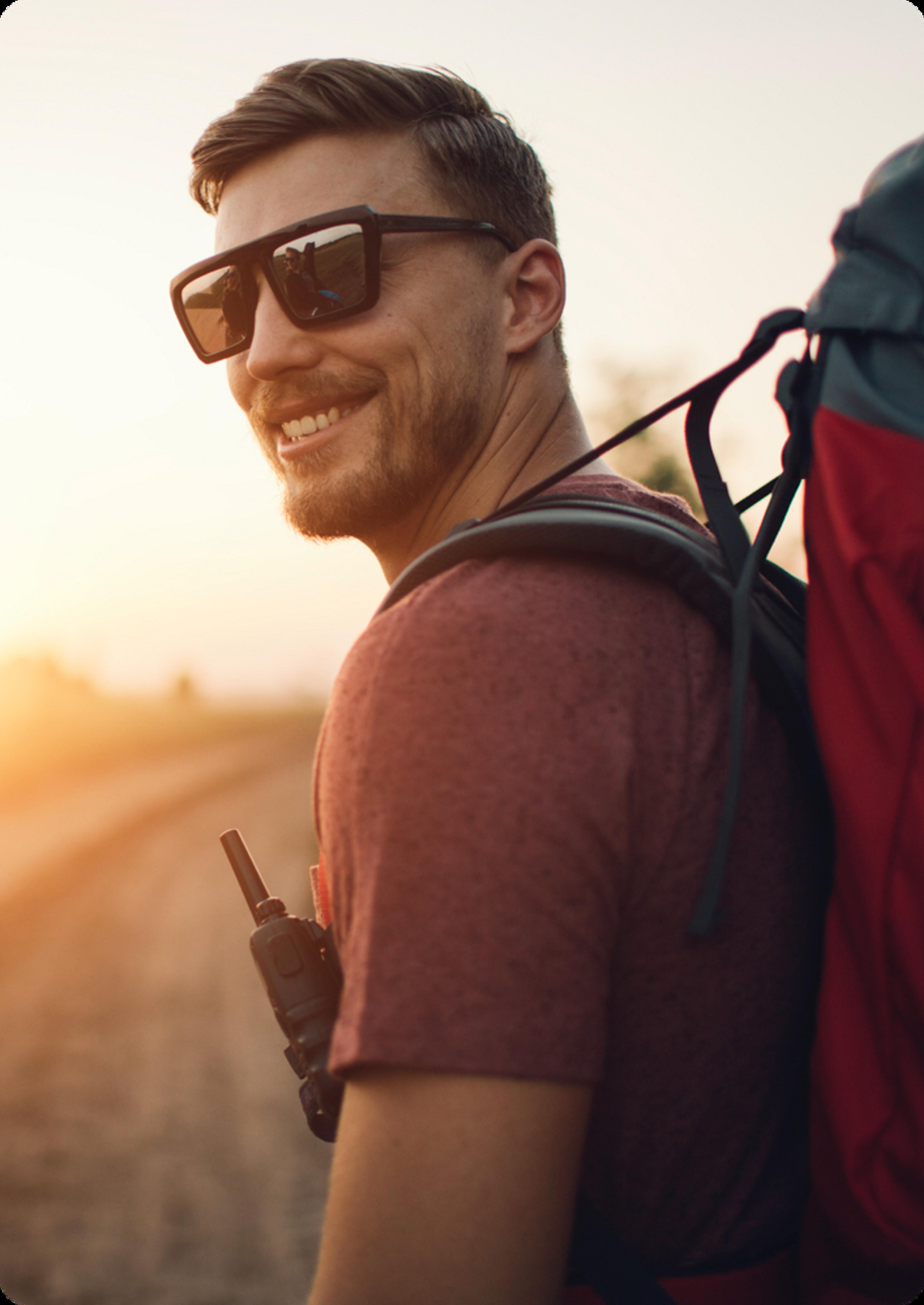 montrant un homme avec des lunettes de soleil et portant un sac à dos