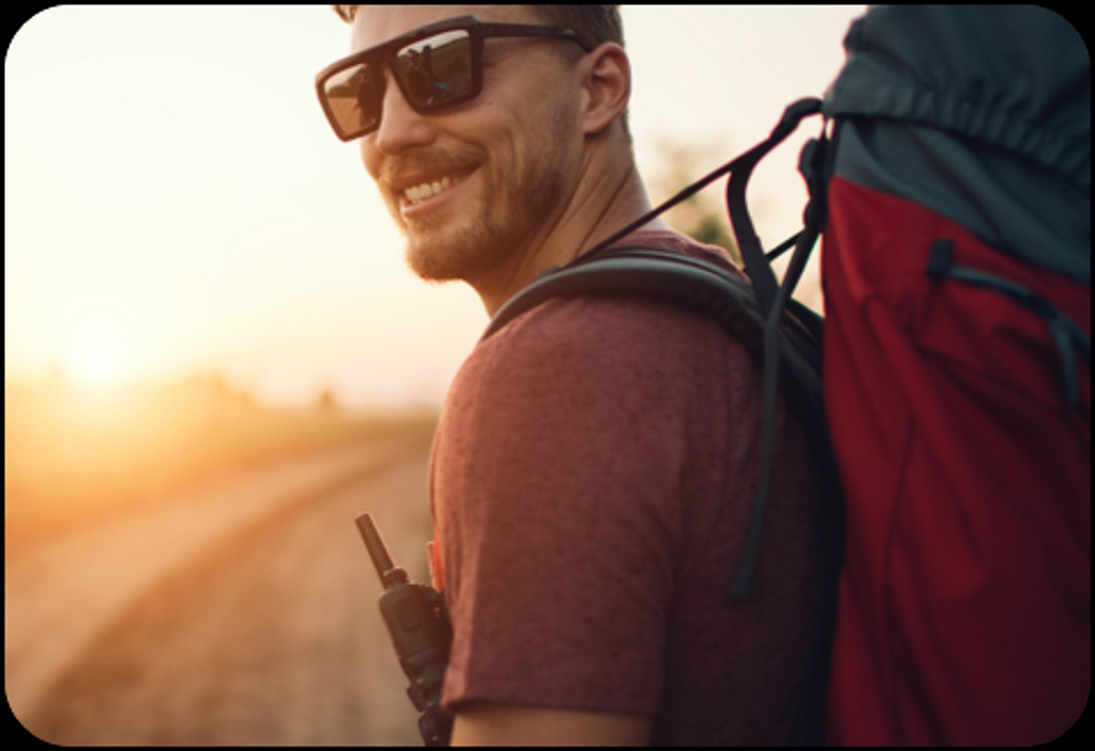photo montrant un homme avec des lunettes de soleil et portant un sac à dos