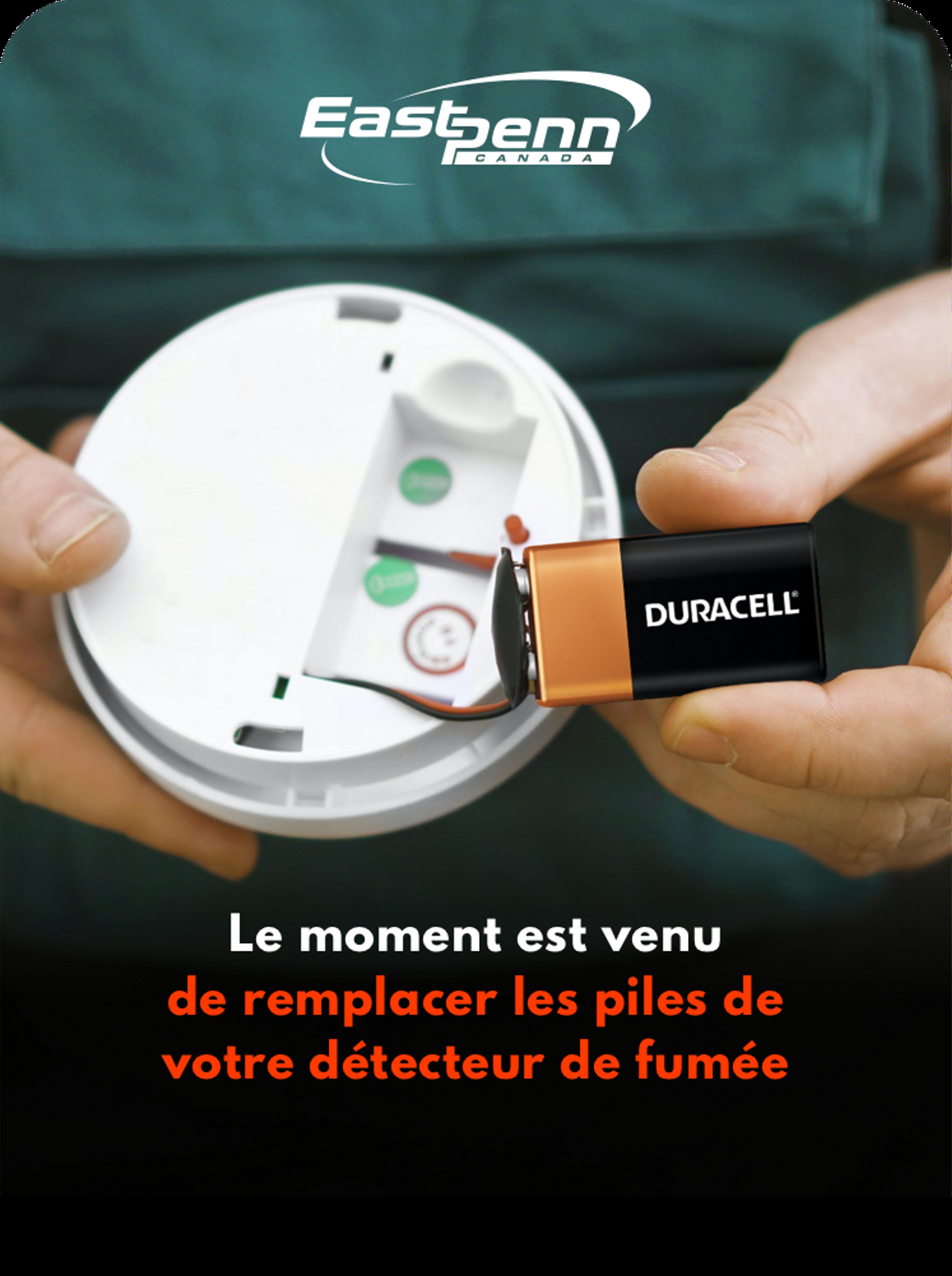 """Image d'un homme tenant un détecteur de fumée et une pile sur fond noir, texte blanc et rouge qui dit """" Il est temps de remplacer les piles de votre détecteur de fumée"""""""
