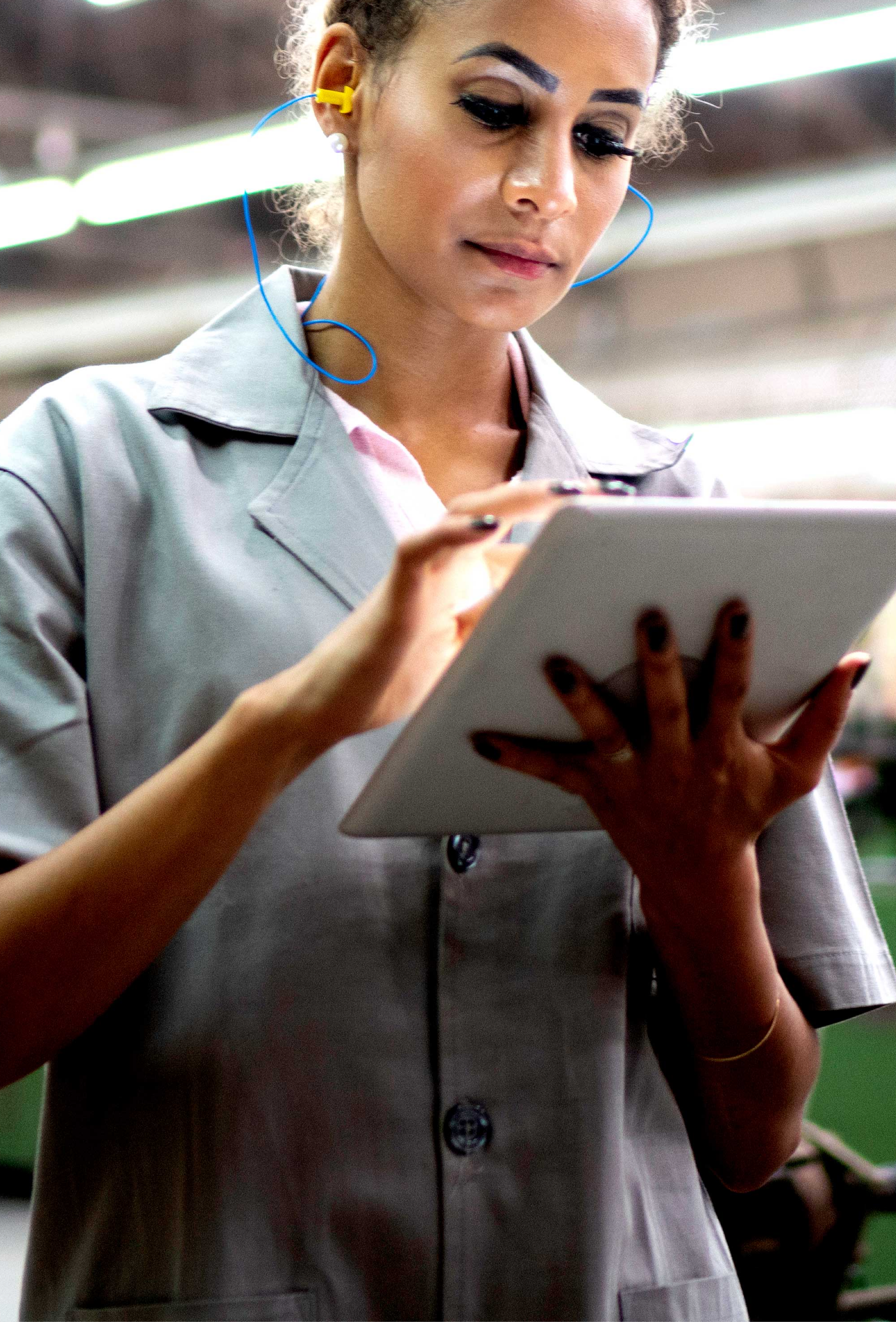 Image of blonde wearing yellow earplugs and  a gray lab coat typing on an ipad