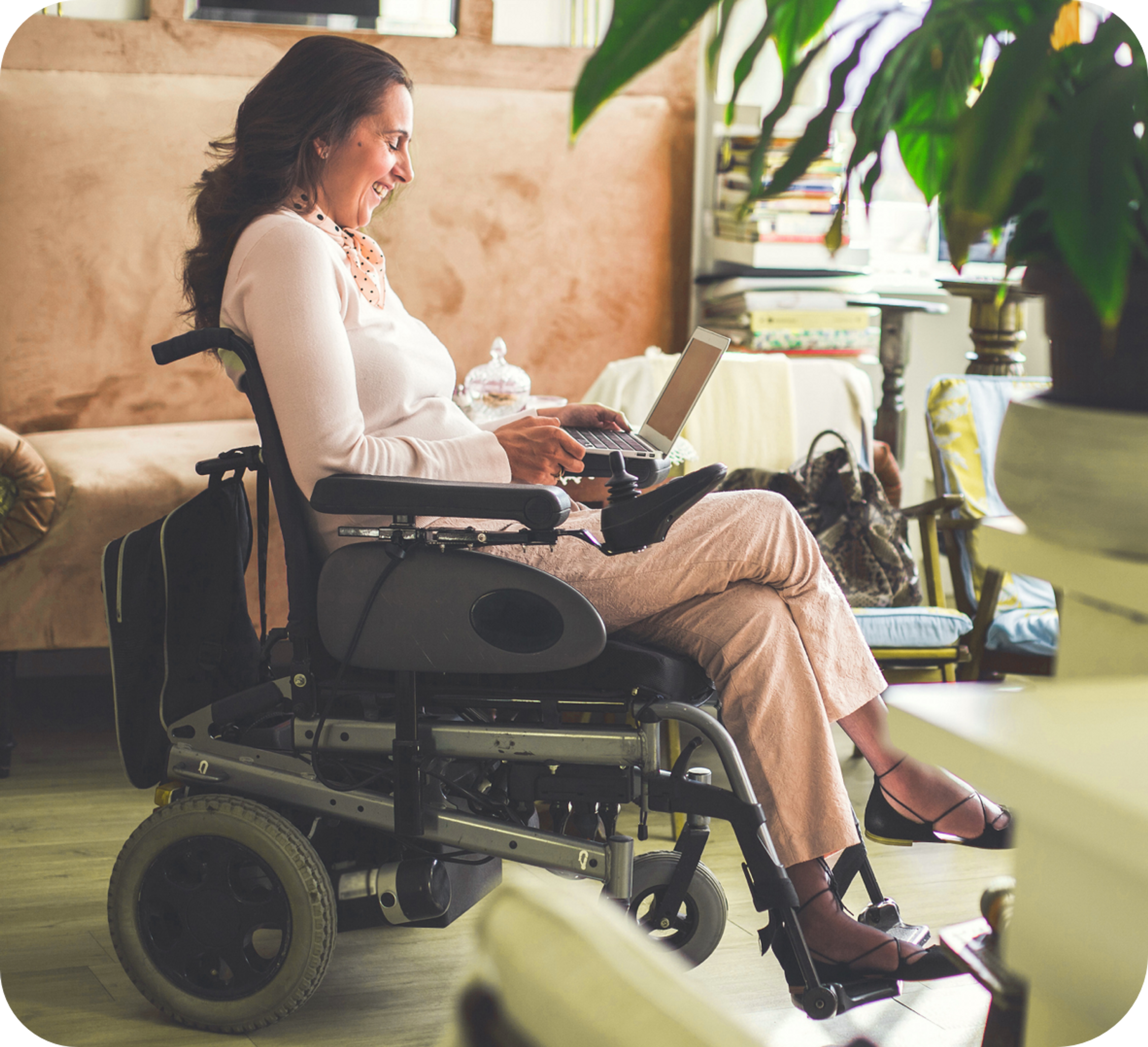 Photo of smiling Caucasian woman sitting on a motorized wheelchair and using her laptop