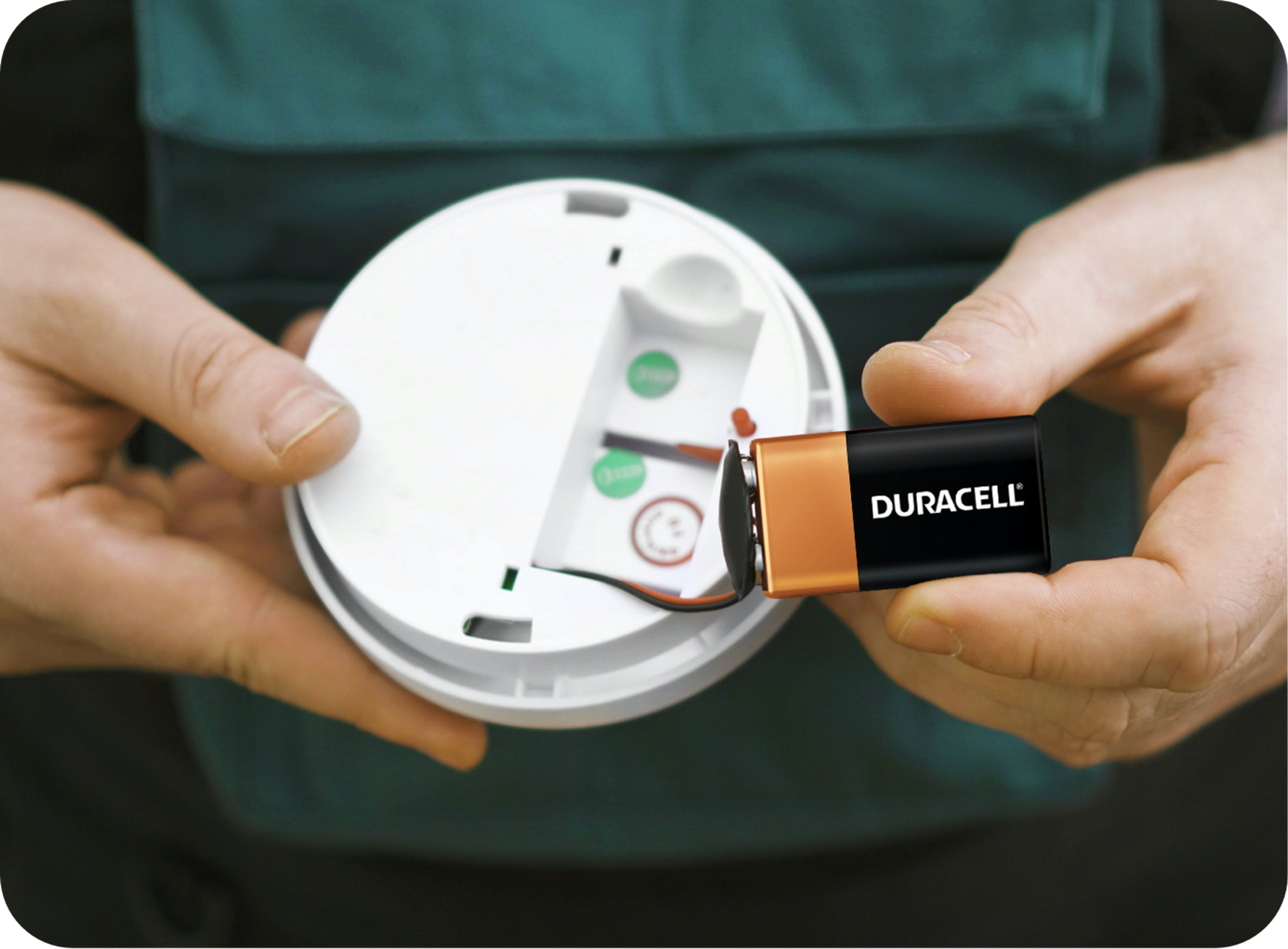 Picture of smoke detector and duracel battery being held by a Caucasian man's hands