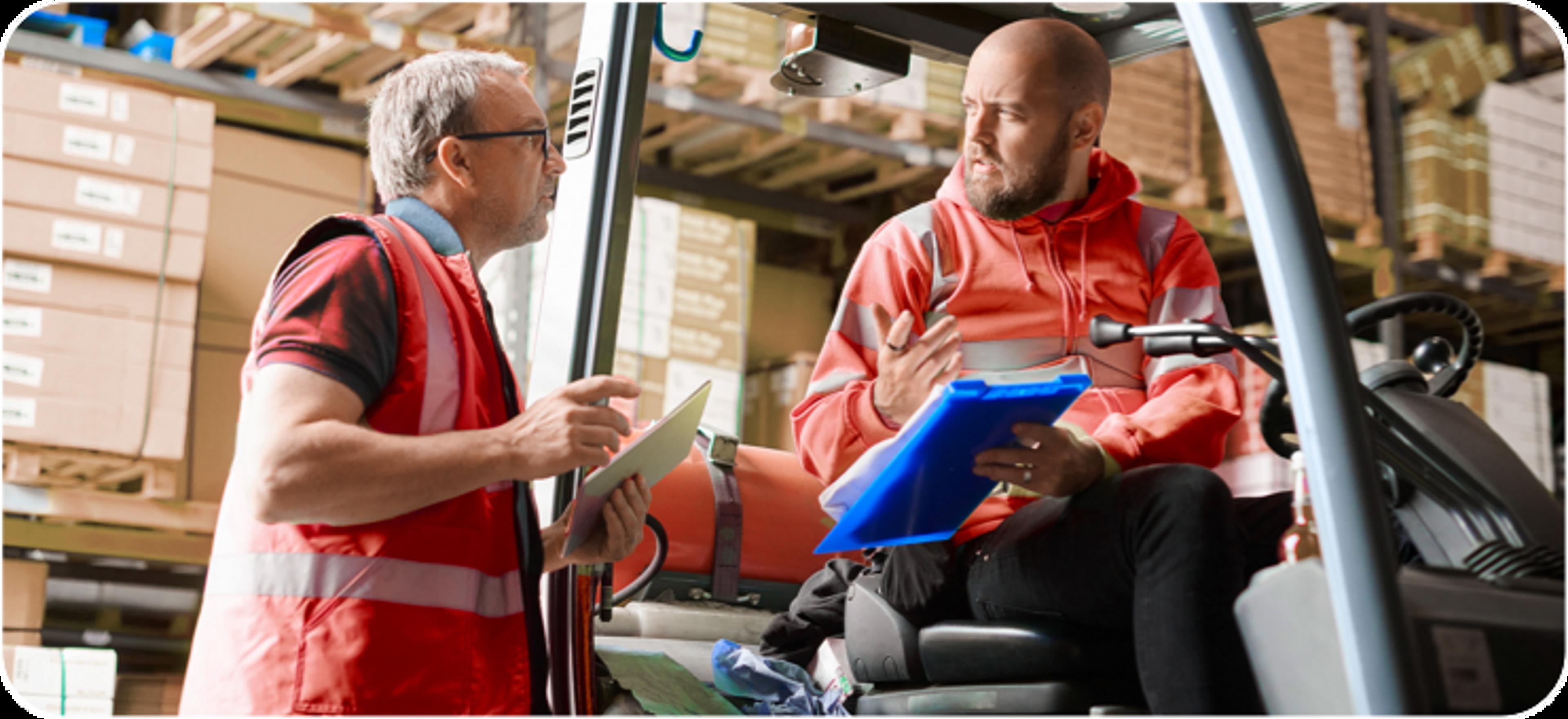 Deux hommes de race blanche portant des vestes de sécurité rouges, discutant dans un entrepôt