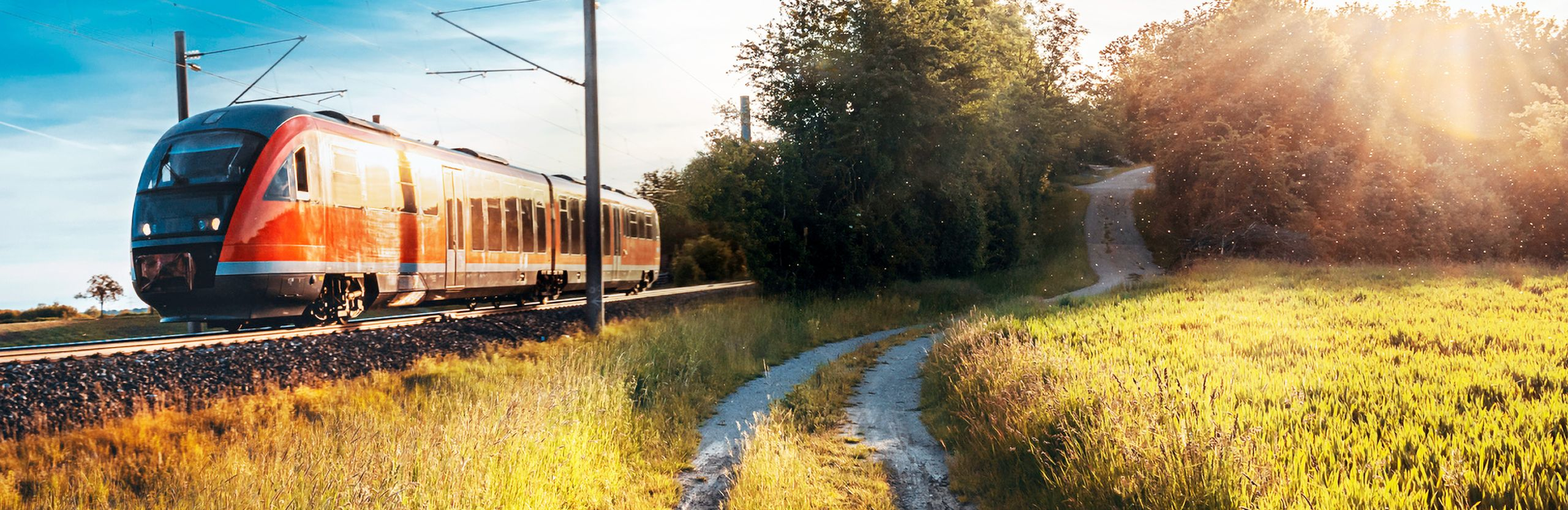 Picture of a locomotive passing through train tracks in a prairie landscape