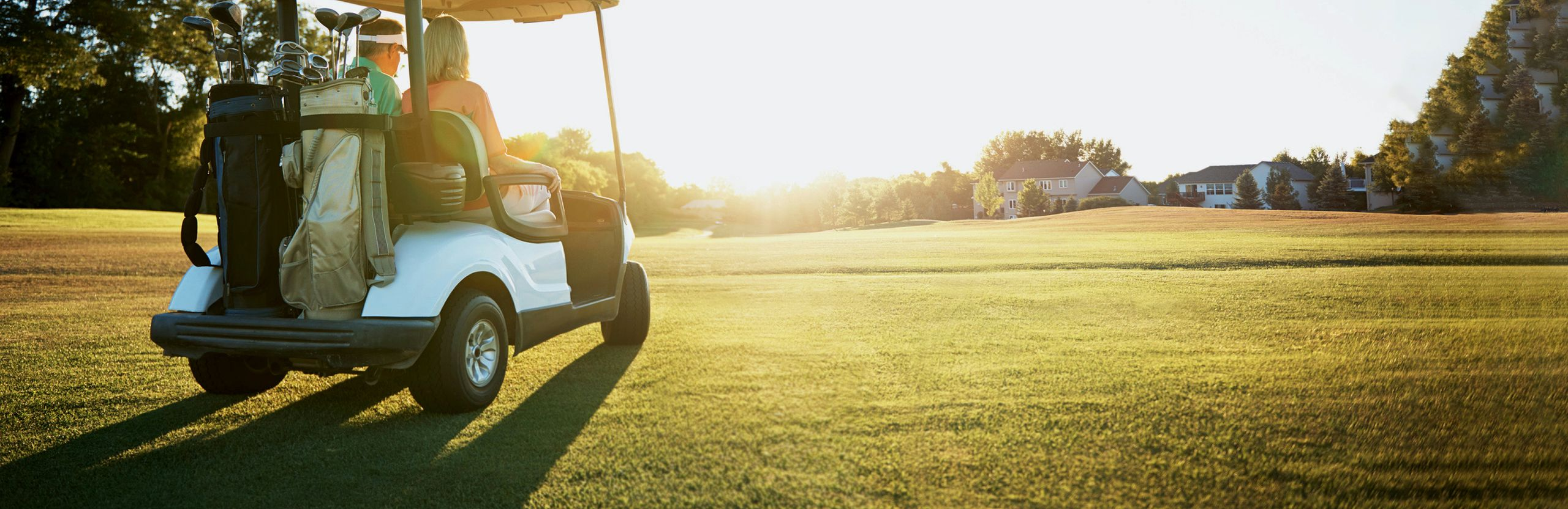 Picture of man and woman driving a golf cart through sunset field