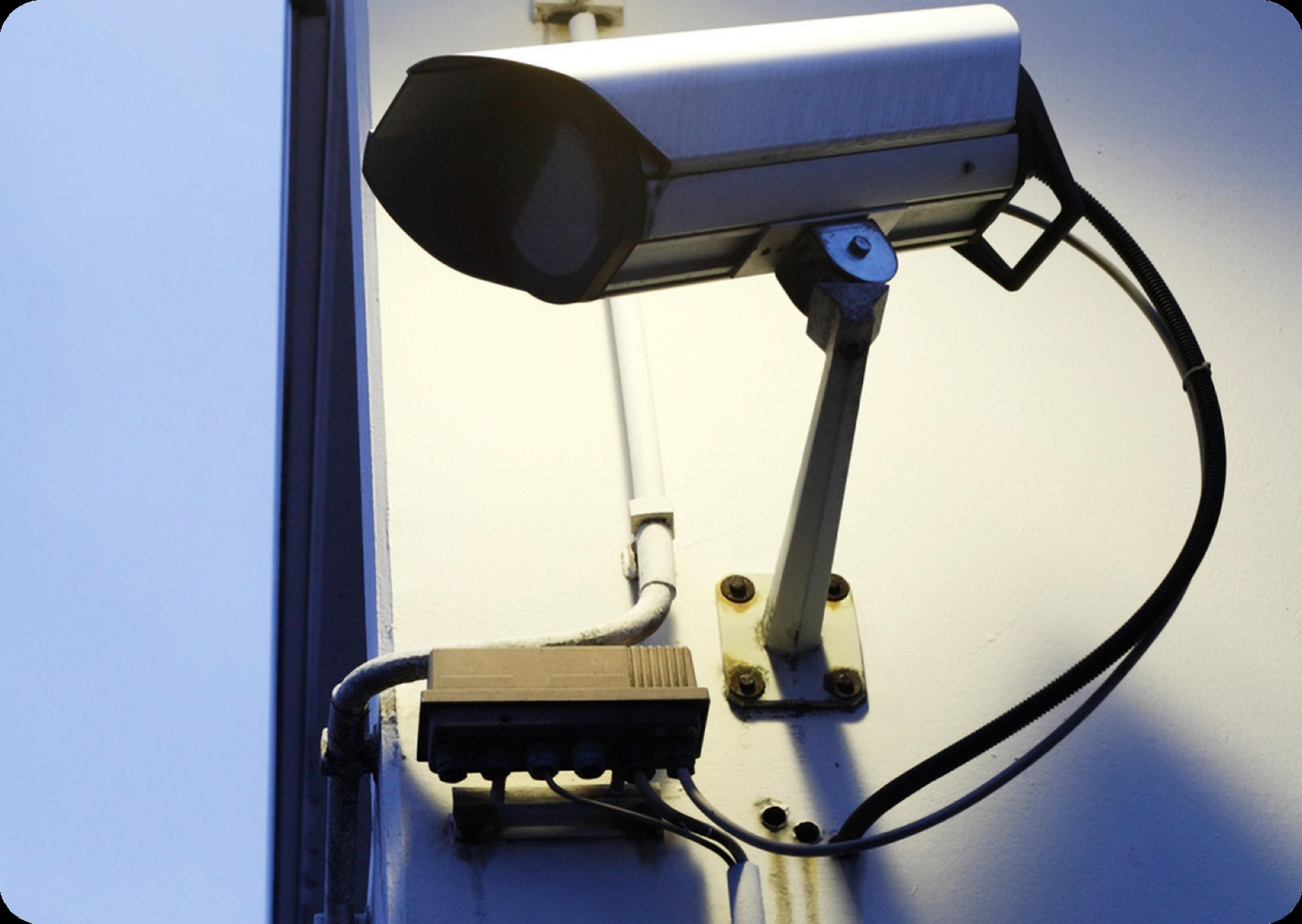 Photo de caméra de sécurité entourée d'un rectangle blanc aux coins arrondis avec le mot « Affaires » en lettres minuscules rouges
