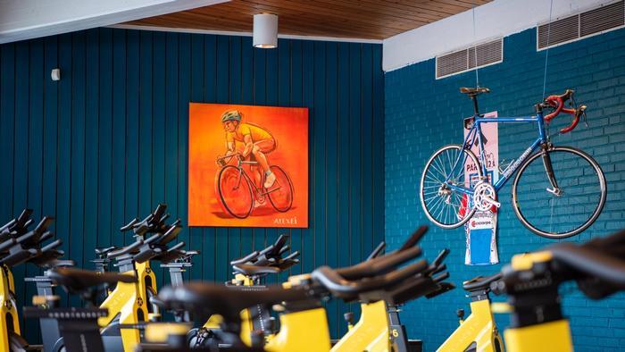 Spinningrom med maleri av syklist på vegg. Gammel sykkel henger fra tak.
