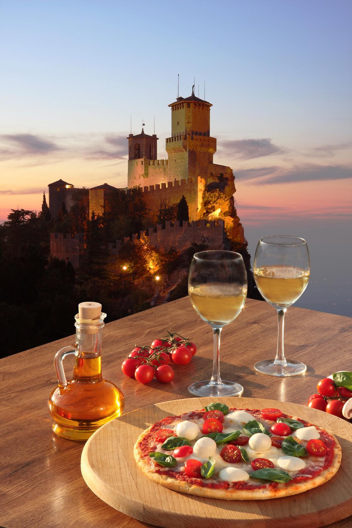 God mat med fin utsikt over italiensk kyst i solnedgang. Pizza med mozarella, tomat og babyleaf. Øl til maten. Oliven som valgfritt tilbehør. Slott i bakgrunnen.