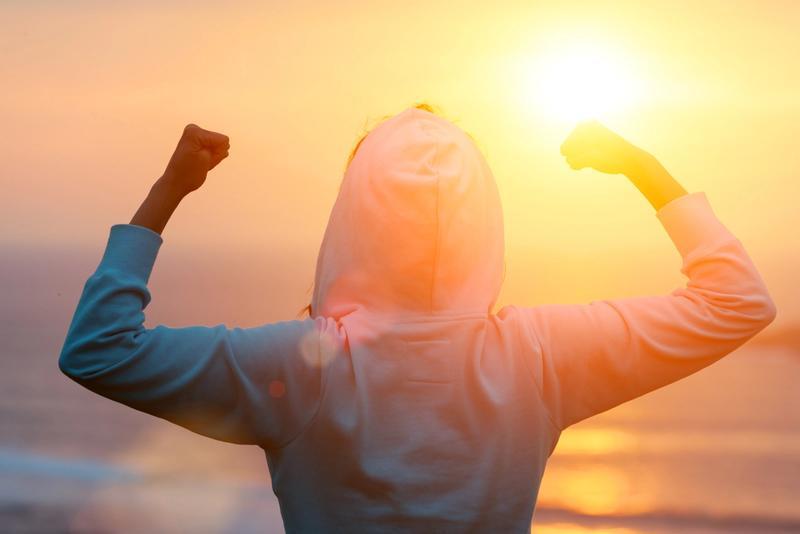 Jente med hettejakke holder hender i været under solnedgang