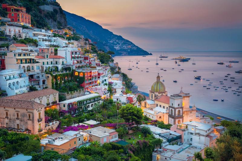 Amalfikysten i Italia ved solnedgang. Gamle bygg og mange båter langs kysten.