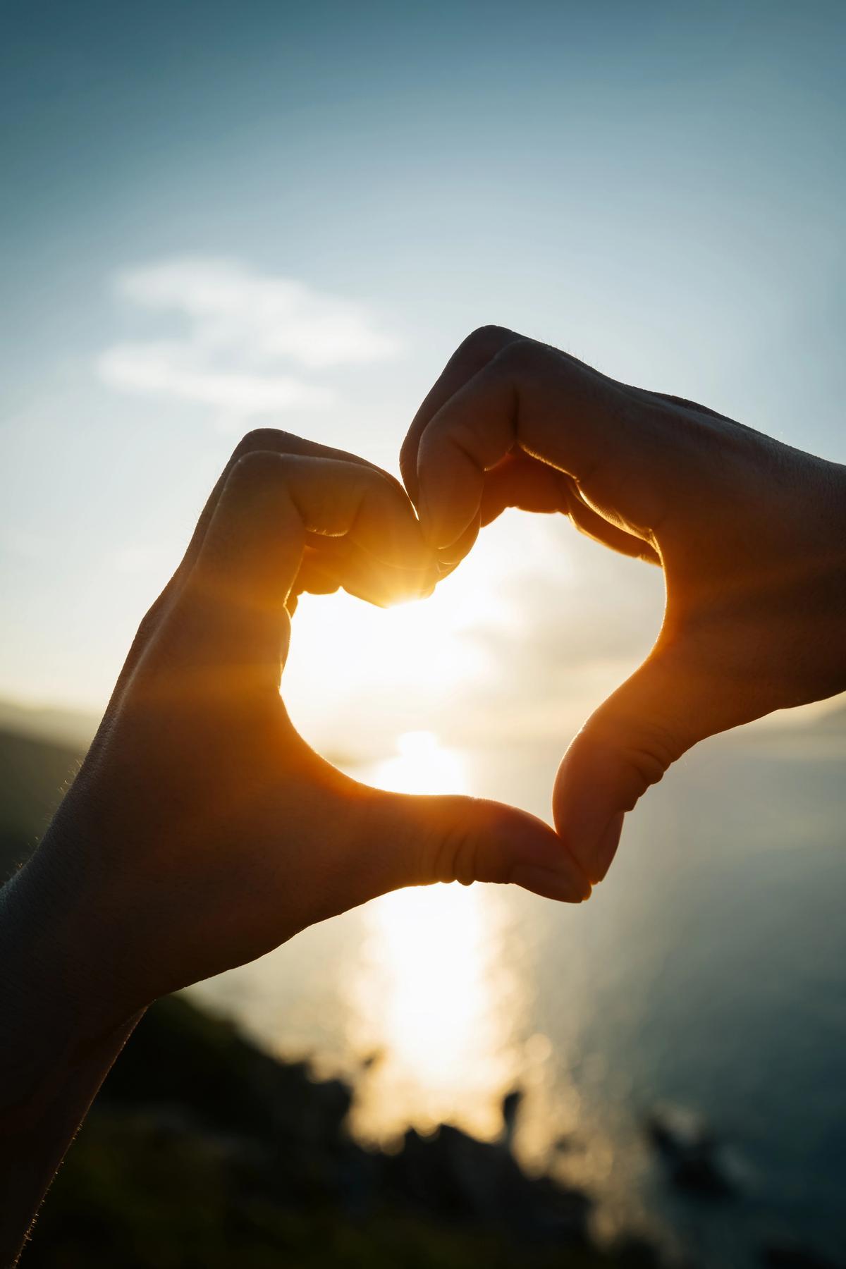 To hender former et hjerte med solen som skinner igjennom