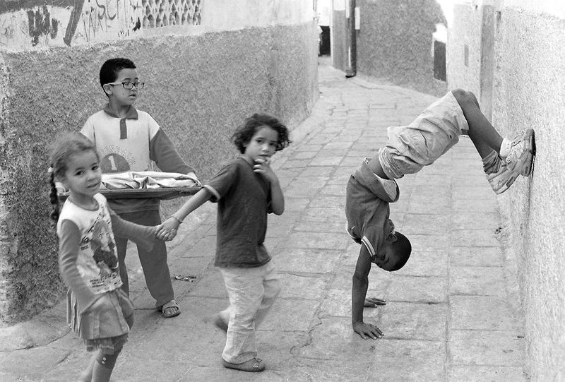 children playing in an alley. one child does a handstand against the wall, two hold hands, another carries a tray of pastries.