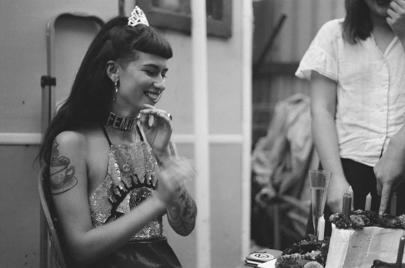 Kate mchugh wearing a tiara sitting in front of a birthday cake smiling