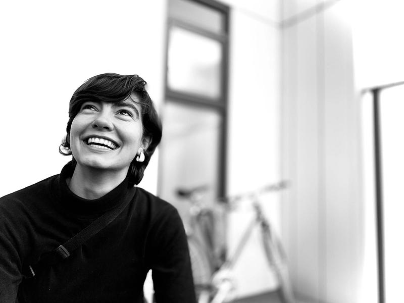 A black and white photo of Michaela smiling wearing a black long sleeved top with white earrings
