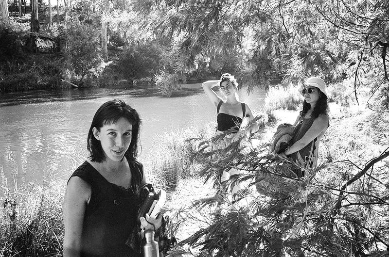 three women stand in front of a river in the sun under trees