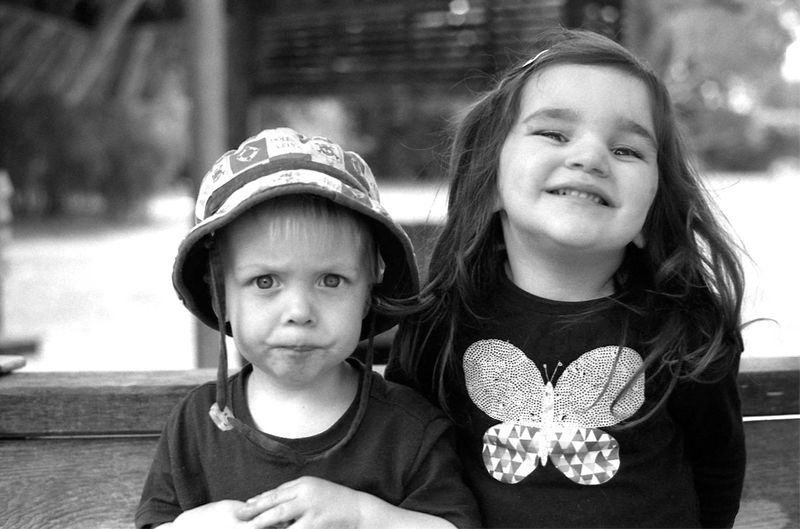two children stand next to each other, one smiling, one frowning.