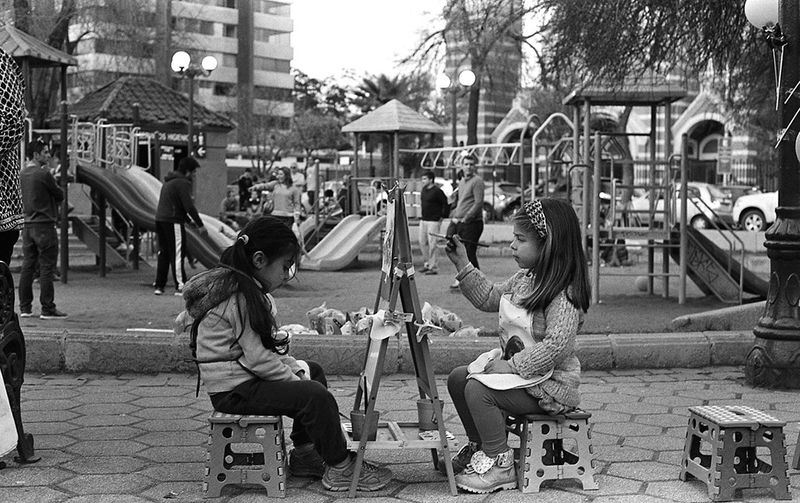two children paint at easels next to a playground