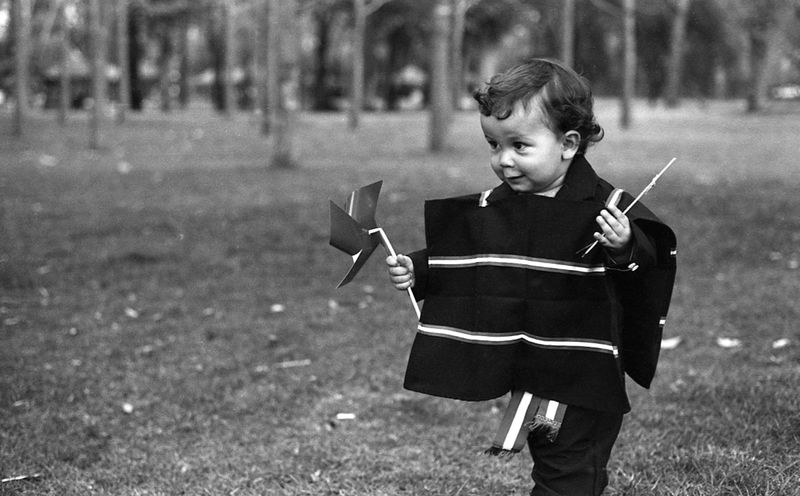 a child holds a pinwheel dressed in traditional chilean costume