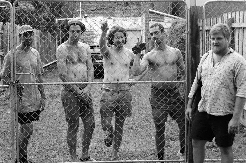 men pose behind a fence