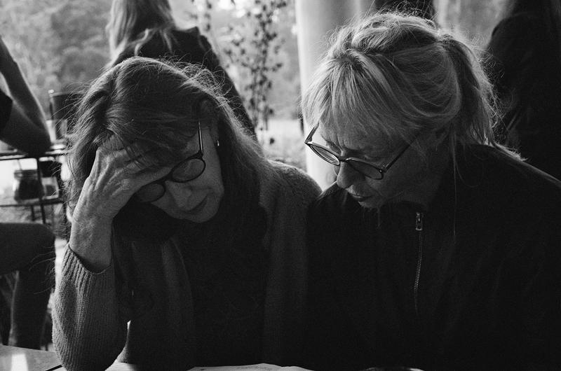 two women at a restaurant look at a menu together